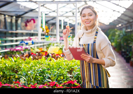 Smiling pretty young woman gardener working in greenhouse and using tablet - Stock Photo