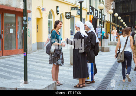 PRAGUE, CZECH REPUBLIC - AUGUST 28, 2015: Woman talking with two nuns in the old town of Prague, Czech Republic - Stock Photo