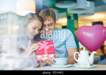 Young surprised woman opening her boyfriend gift in cafe - Stock Photo