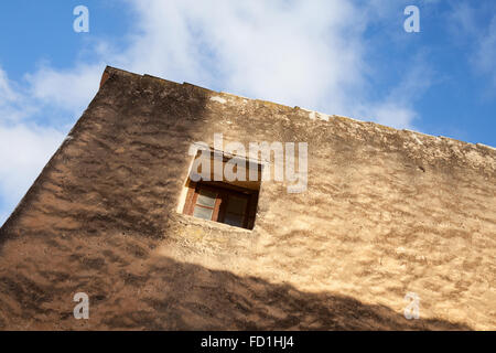 Small window in old stone wall, under blue cloudy sky - Stock Photo