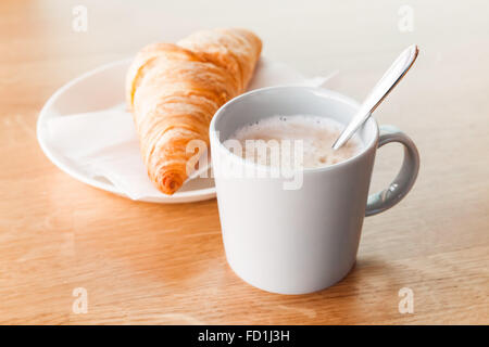 Cappuccino with croissant. Cup of coffee with milk foam stands on wooden table, closeup photo with selective focus - Stock Photo