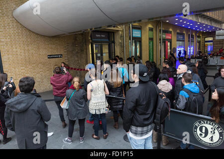 A queue of people waiting at platform 9 3/4 at Kings Cross station - Stock Photo