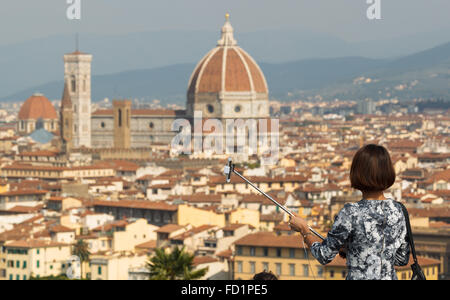 A young woman preparing to take a selfie in Piazzale Michelangelo, Florence, Tuscany, Italy. - Stock Photo