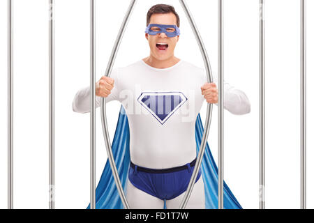 Young man in superhero costume breaking out of prison by bending the bars isolated on white background - Stock Photo