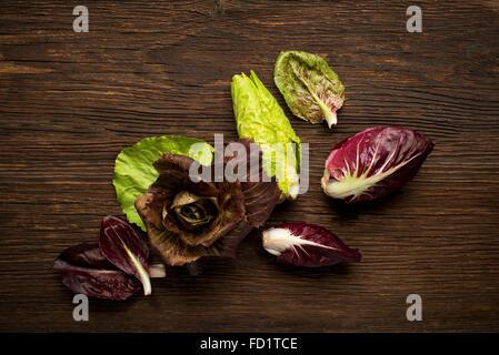 Fresh mixed radicchio on a wooden background. - Stock Photo