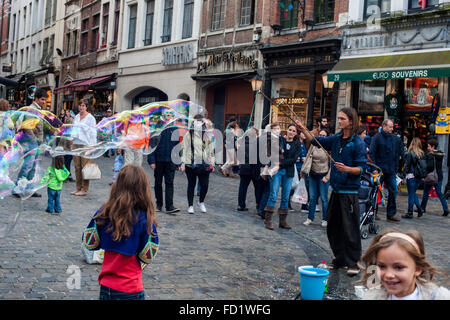 A street artist makes giant soap bubbles around Grand in Brussels - Stock Photo