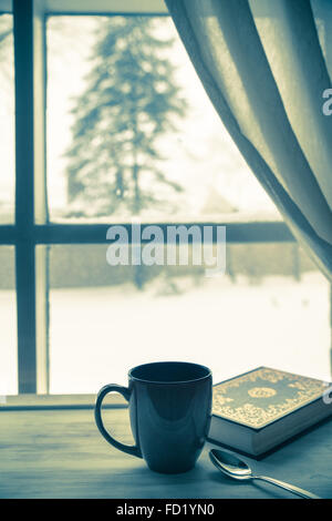 cozy home still-life of mug of coffee and book new snowy window after winter storm - Stock Photo