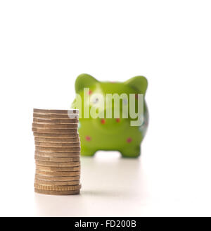 Pile of Euro coins in front of a green piggy bank, selective focus on foreground - Stock Photo
