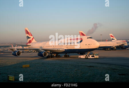 Passenger jet being towed by a tractor at London Airport UK - Stock Photo