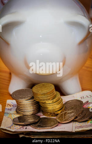 White coloured ceramic piggy bank with bank notes and some GBP coins - Stock Photo