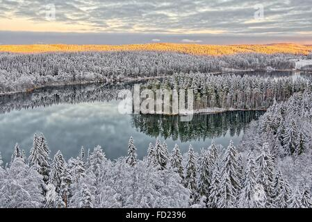 Aerial view of snowy lake and forest at Aulanko nature park in Finland. Late afternoon Sun shining in frozen landscape. - Stock Photo