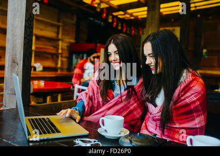 two girls watching something in laptop - Stock Photo