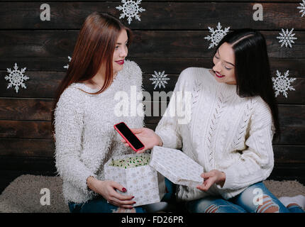 Two young girls holding holiday present - Stock Photo