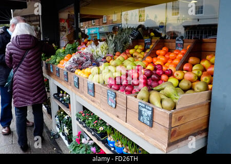 A display of fresh fruit for sale outside of a greengrocers shop on a high st in an english town - Stock Photo