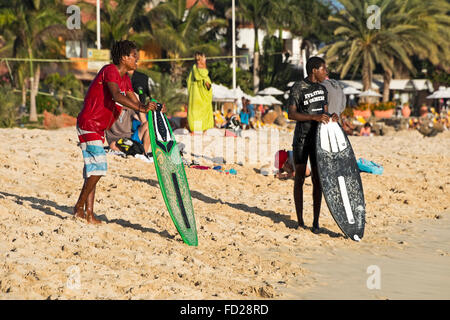 Horizontal portrait of skim boarders standing on the beach waiting for the perfect wave in Cape Verde. - Stock Photo