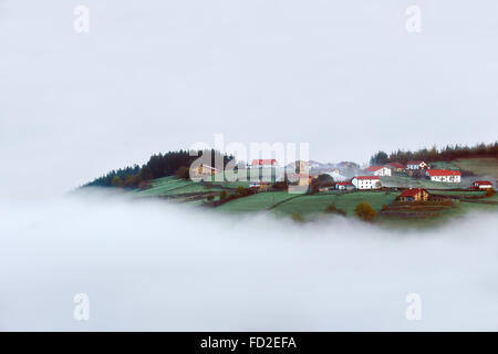 village and houses in Aramaio valley surrounding by fog - Stock Photo