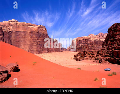 Four wheel drive in Wadi Rum, Jordan. Blue sky fades to red sand with tourists in 4wd on a tour in this desert. - Stock Photo