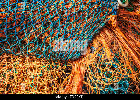 An abstract image of blue and orange fishing nets. - Stock Photo