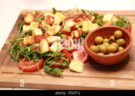 Haloumi cheese,Rocket and Tomato salad with green olives - Stock Photo