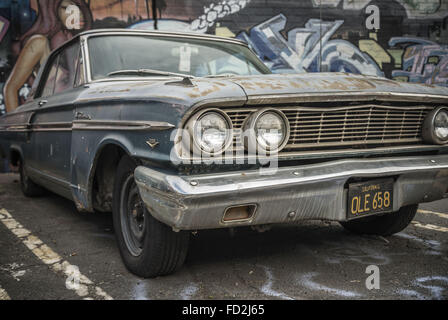 Los Angeles, California, USA. 9th Jan, 2015. A '65 Ford Fairlane sits in front of a mural-covered wall in the Arts - Stock Photo