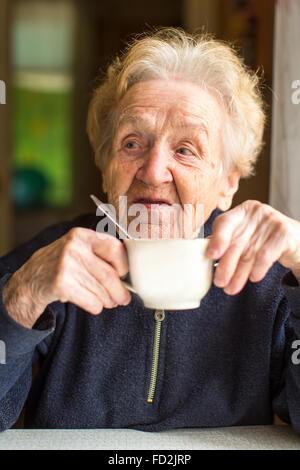 Portrait of an elderly woman drinking tea. - Stock Photo