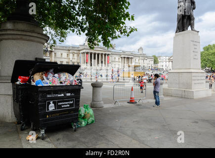 Overflowing commercial waste container full with garbage on Trafalgar Square, London - Stock Photo