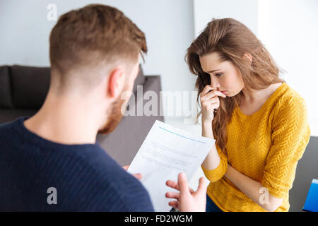 Worried couple discussing about domestic finances at home - Stock Photo