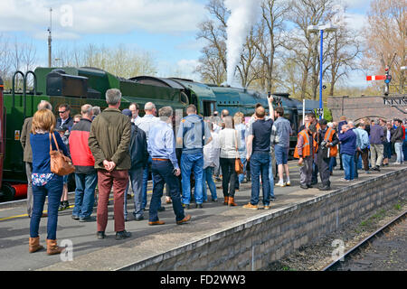 Railway enthusiasts gather around  preserved engine 34046 Braunton hauling steam train at Banbury station during - Stock Photo