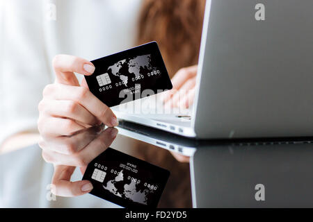 Closeup portrait of woman shopping online on laptop computer with credit card - Stock Photo