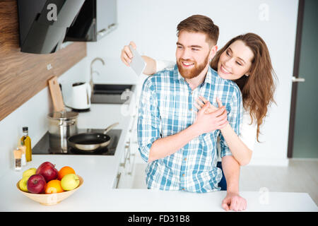 Portrait of a smiling couple making selfie photo on smartphone at the kitchen - Stock Photo
