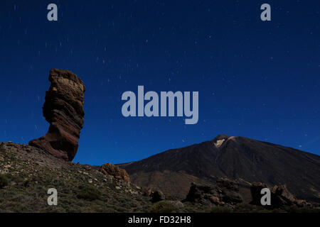 Stars trail in the night sky above Los Roques de Garcia and Mount Teide in Teide National Park on Tenerife, Spain. - Stock Photo