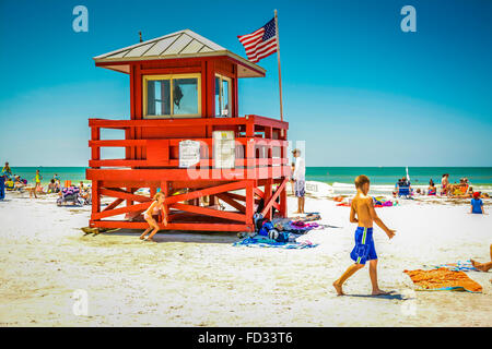 Kids playing on the beach on a hot sunny day amongst the sunbathers near the iconic red lifeguard station on Siesta - Stock Photo