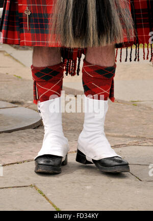 legs and footwear of a standing Scottish man dressed in a red checked tartan kilt. - Stock Photo