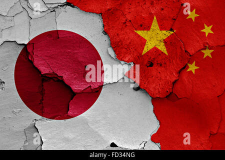 flags of Japan and China painted on cracked wall - Stock Photo