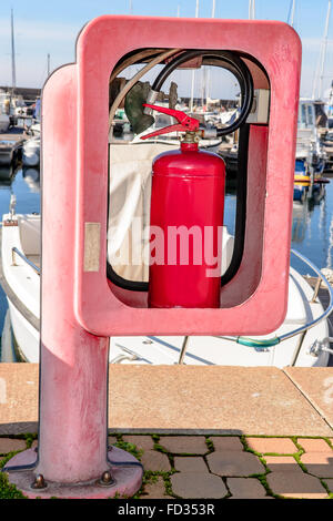 Red fire extinguisher in box on dock railing. - Stock Photo