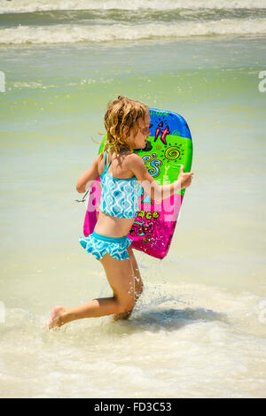 Young Little blonde girl in bathing suit runs in the surf along the seashore at the beach with her colorful boogie - Stock Photo