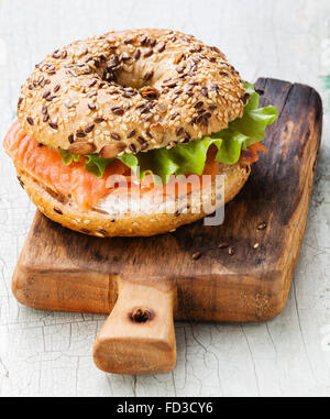 Salmon Bagel Sandwich with cream cheese and grain on blue wooden background - Stock Photo