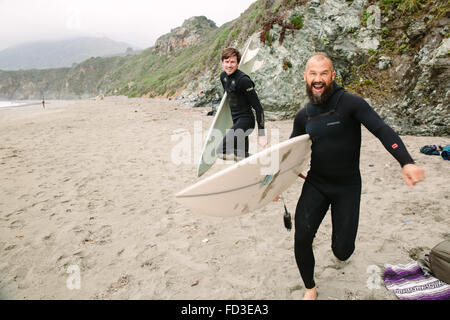 Two surfers goof around on the beach before jumping in the water to catch waves in Big Sur, California. - Stock Photo