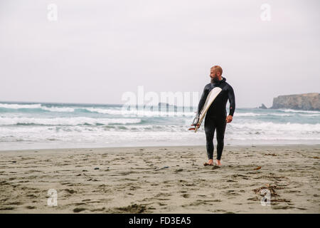 A surfer walks in from the water after a day out on the waves in Big Sur, California. - Stock Photo