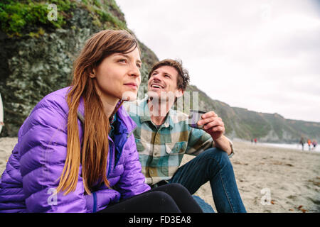 A young couple enjoying an afternoon on the beaches of Big Sur, California. - Stock Photo