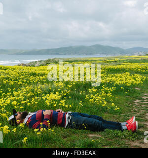 A man rests in a field of yellow flowers on the shoreline of Big Sur, California. - Stock Photo