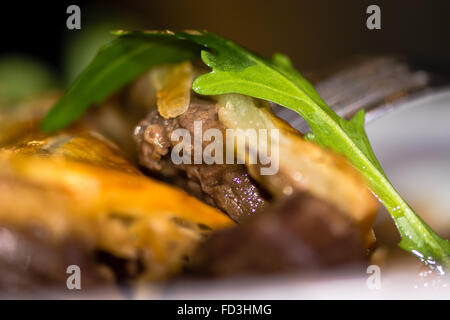 Steak and kidney pie close up of meat with rocket leaf. French restaurant cuisine influenced by traditional English - Stock Photo
