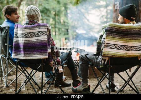 Three friends sit around a campfire in Big Sur, California. - Stock Photo