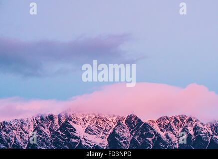 The Remarkables lit up by a pink sunset in beautiful Queenstown, New Zealand. - Stock Photo