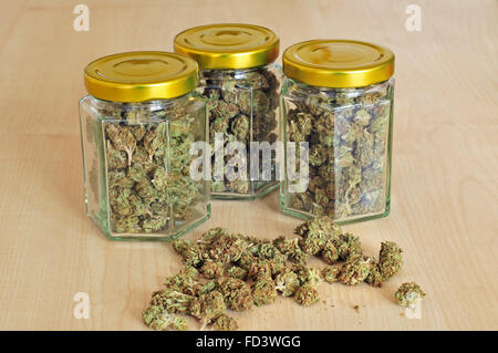 Dry cannabis buds stored in a glass jars - Stock Photo