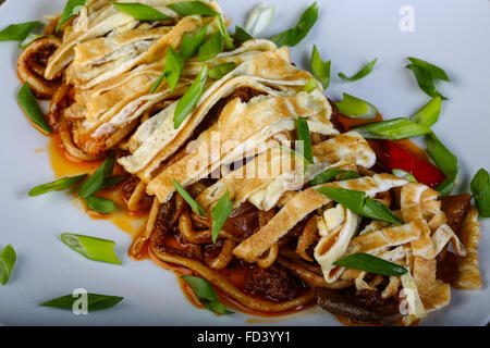 Pasta with omelet and beef served green onion - Stock Photo