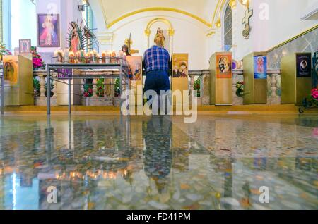 A christian catholic man kneeling and praying on the side altar of Catedral de Nuestra Senora de Guadalupe, a church - Stock Photo