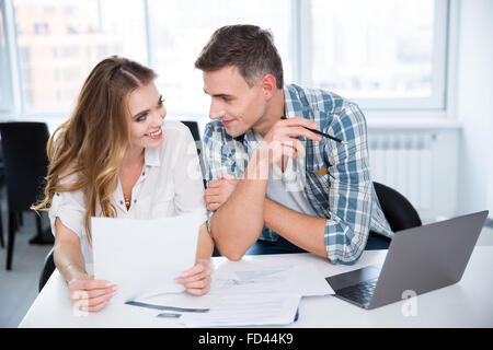 Cheerful man and woman working and flirting on business meeting - Stock Photo
