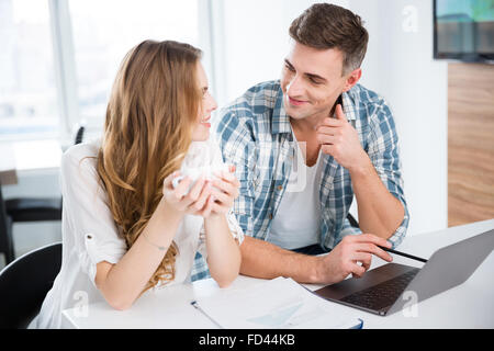 Smiling colleagues in casual clothes working with laptop and drinking coffee - Stock Photo
