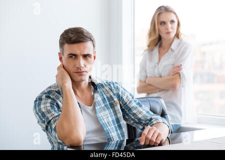 Upset man and woman having difficulties and problems in relationships - Stock Photo